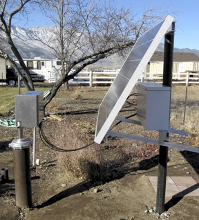 Well casing with mounted motorized pump. Solar panel on stand showing battery box and cables.
